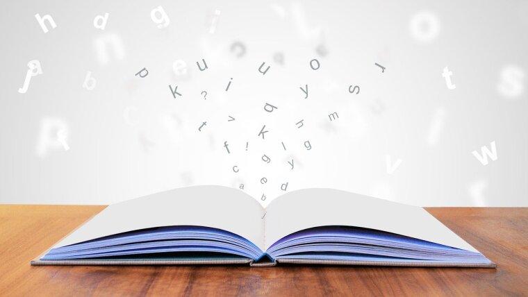 Buchstaben fliegen über Buch